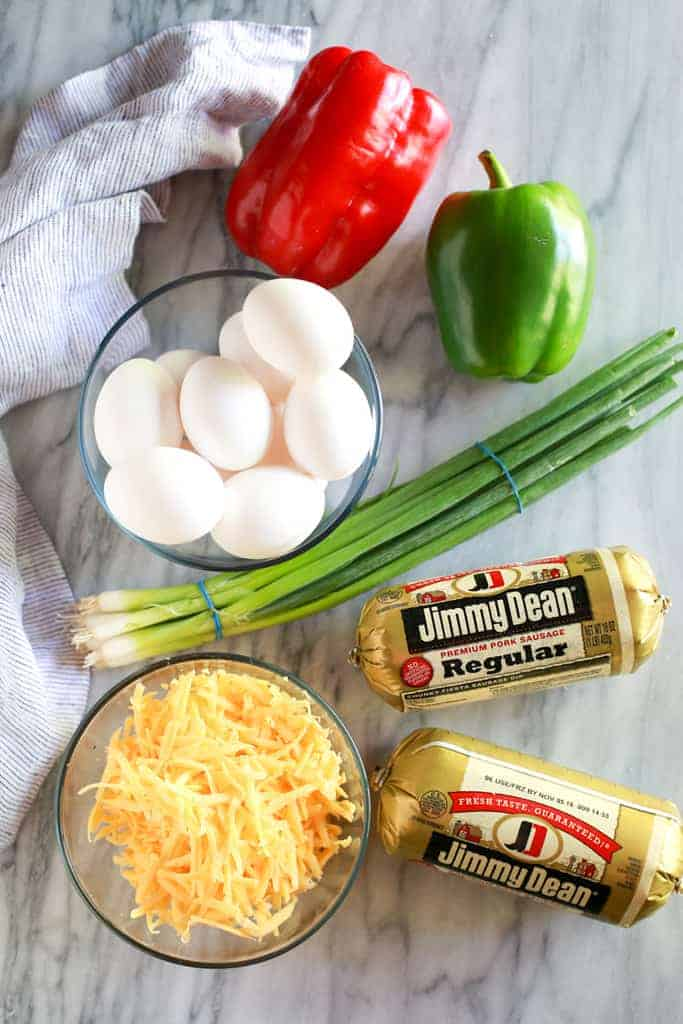 An overhead photo of the ingredients for breakfast casserole including eggs, red and green bell pepper, green onion, sausage and shredded cheddar cheese.