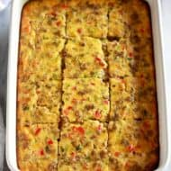 Breakfast casserole baked in a 9x13'' white pan and cut into twelve servings.