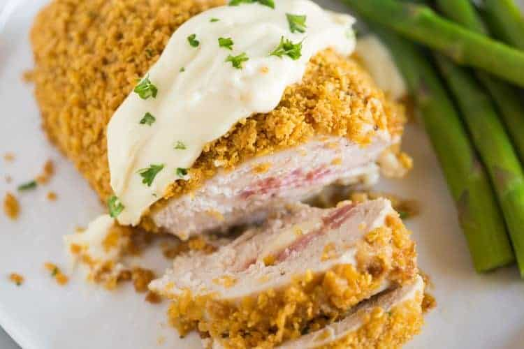 Chicken cordon bleu with crushed cornflakes and a sauce on top, served on a white plate with a side of asparagus.