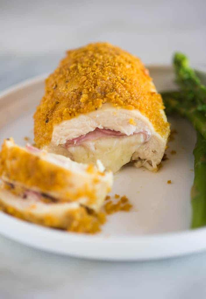 Chicken cordon bleu with a slice cut out to show ham and cheese in the center.