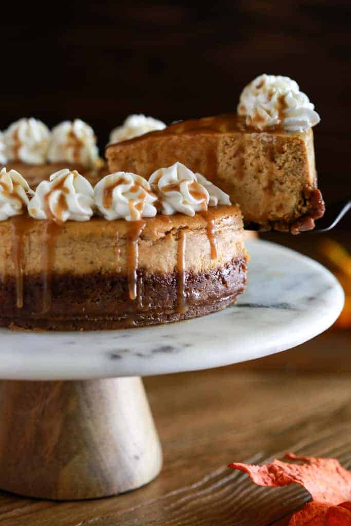 Pumpkin cheesecake on a cake stand with a slice being removed.