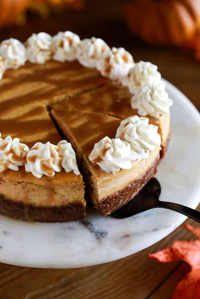 Overhead view of a pumpkin cheesecake with caramel sauce and whipped cream and a slice being served from it.