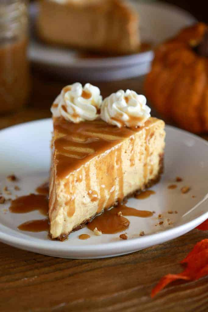 A slice of pumpkin cheesecake on a white plate with caramel sauce drizzled on top.