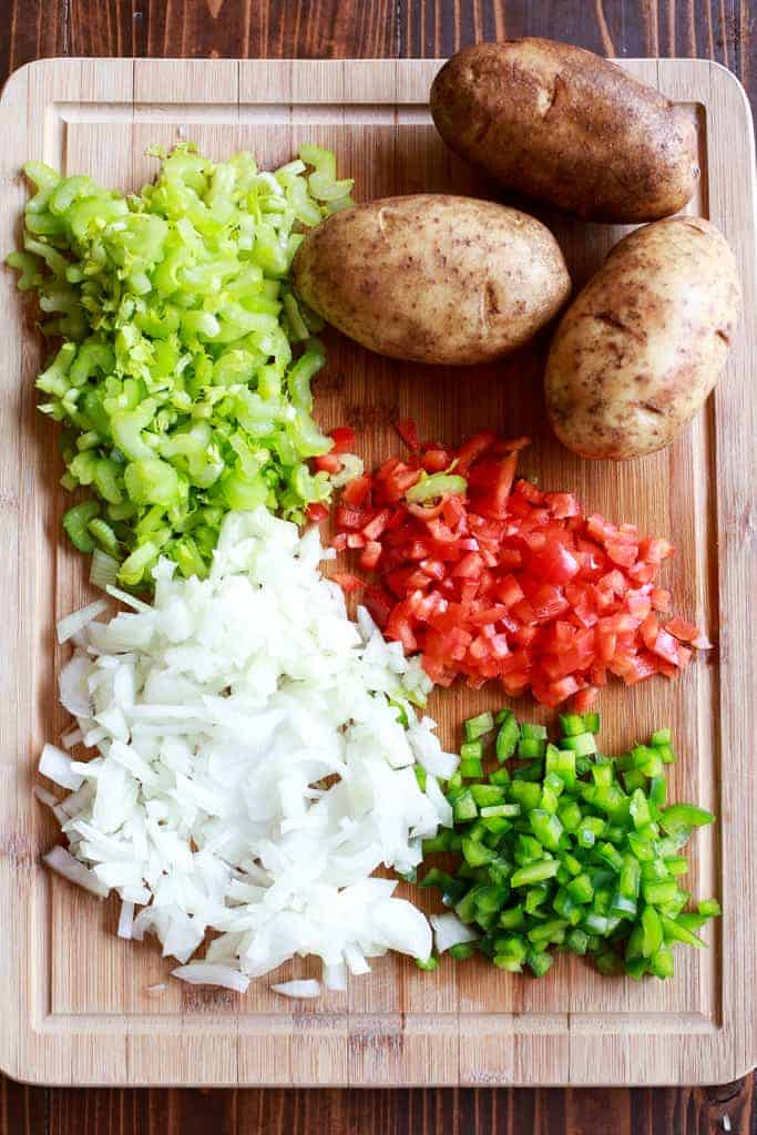 Overhead photo of a wood cutting board with the ingredients for clam chowder, including potatoes, chopped celery, onion and bell peppers.