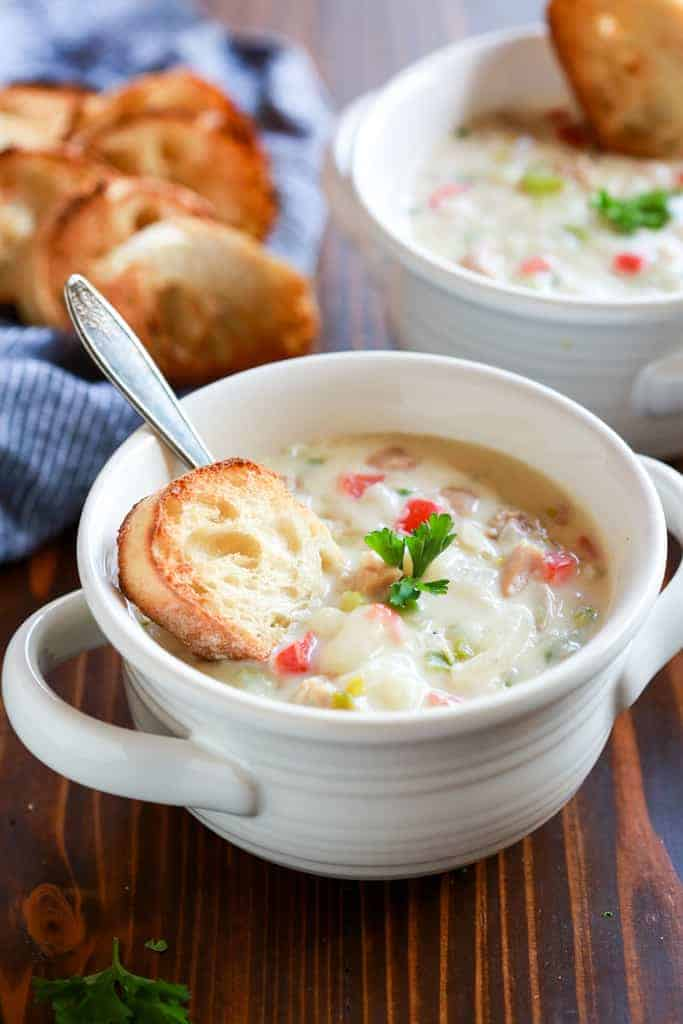 Two bowls of clam chowder on a wood board with a napkin and slices of toasted bread in the background.