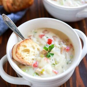 A small white soup bowl filled with clam chowder with a crusty piece of bread and spoon in it and another soup bowl and extra bread slices in the background.