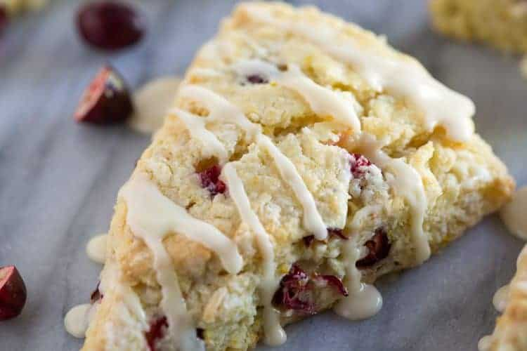 A cranberry orange scones with glaze on a marble board with more scones and fresh cranberries in the background.