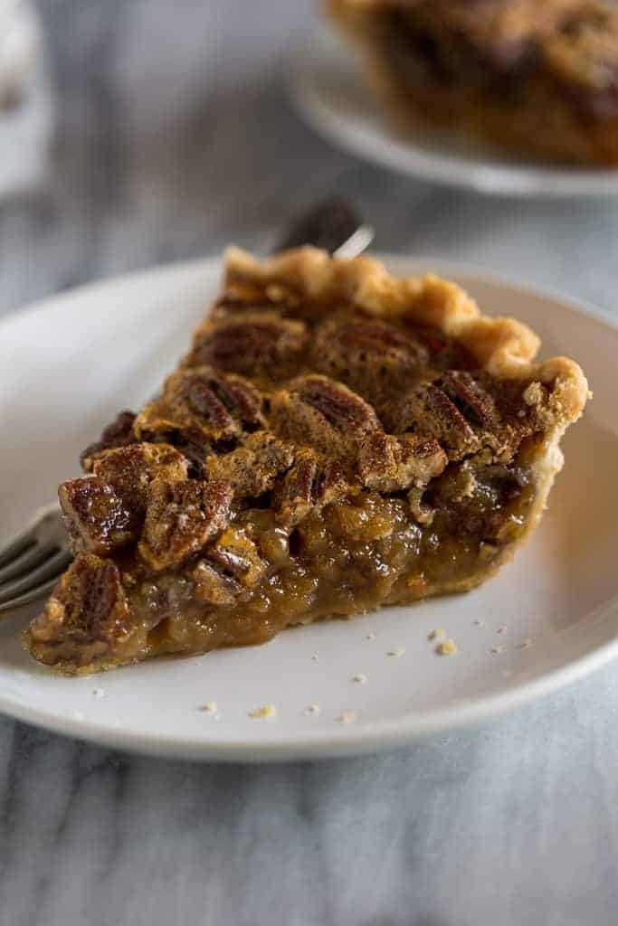 A slice of pecan pie on a white plate with a fork.