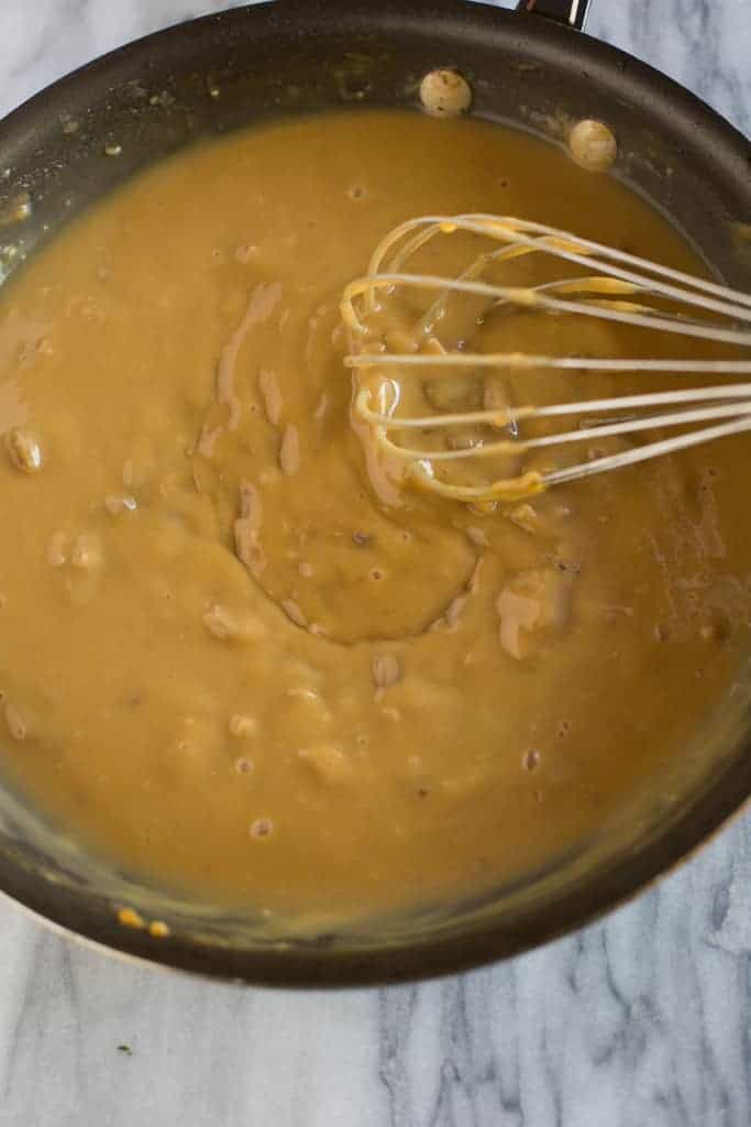 A saucepan with turkey gravy with giblets and a wire whisk.