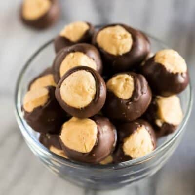 A small glass bowl filled with buckeye peanut butter balls which are a no bake candy made with peanut butter, powdered sugar and dipped in chocolate.