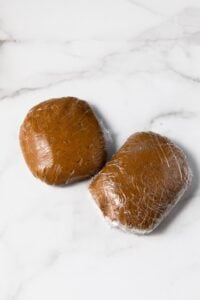 Two balls of gingerbread dough wrapped in plastic wrap.