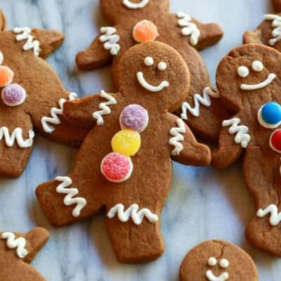Gingerbread cookies decorated as gingerbread men with white frosting and colored gumdrops.