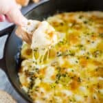 A cast iron skillet with baked fontina cheese dip, bread slices in the background and a hand taking a scoop out of the cheese dip with a bread slice.