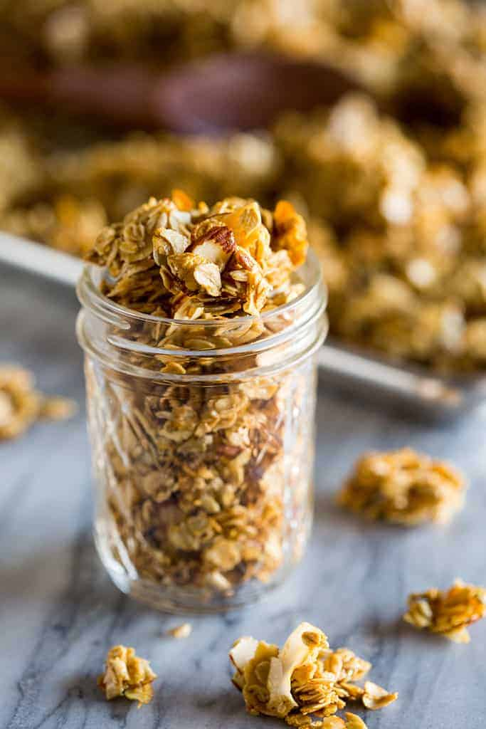 A mason jar filled with homemade granola and a sheet pan of baked granola in the background.