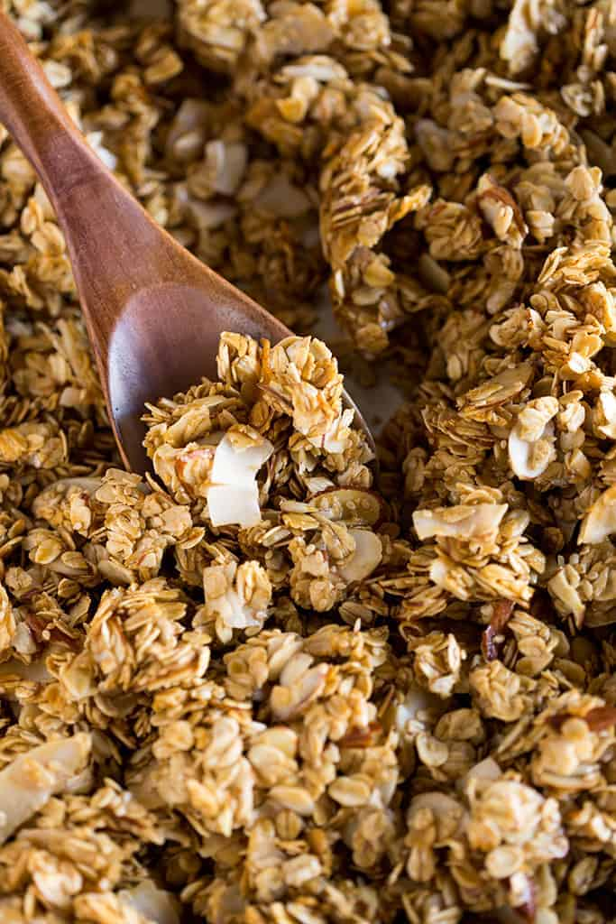 A close up photo of a granola in a sheet pan after it's been baked and a wooden spoon scooping some of it.