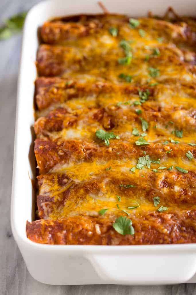Chicken enchiladas with red enchilada sauce served in a white baking dish.