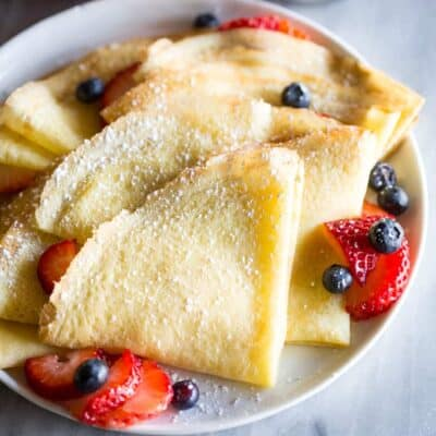 Crepes folded into fourths and sprinkled with powdered sugar, layered on a white plate with sliced strawberries and blueberries.