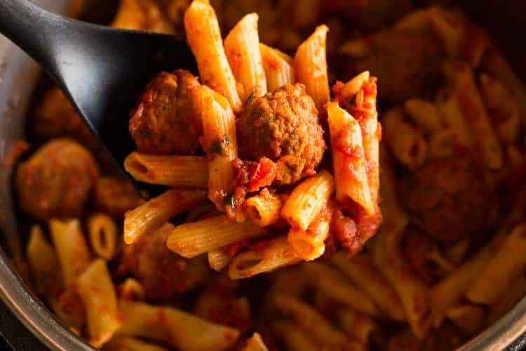 Overhead photo of an instant pot filled with penne pasta in a red sauce with meatballs, and a spoonful being lifted out.