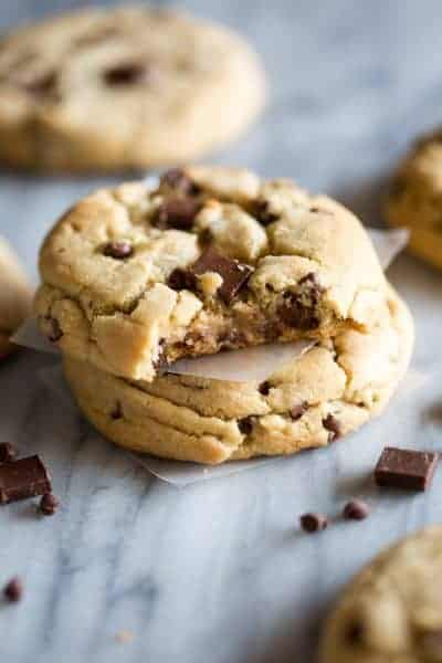 Two Jumbo Chocolate Chip Cookies stacked on top of each other with a bite taken out of the top cookie.