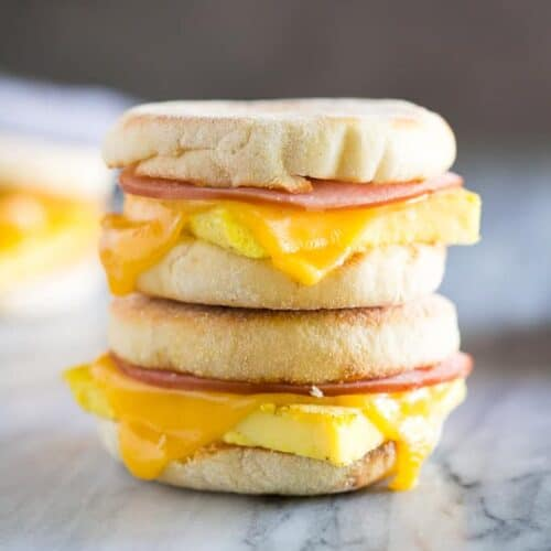 Two egg, ham and cheese breakfast sandwiches made on English muffins, stacked on top of each other.