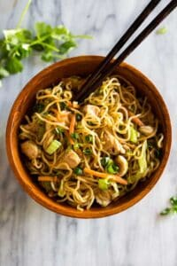 Overhead photo of chicken chow mein served in a wooden bowl with chopsticks.