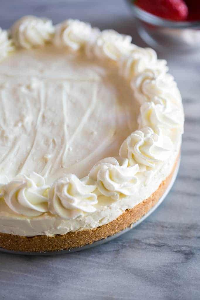 No Bake Cheesecake with a graham cracker crust and whipped cream roses piped around the edges.