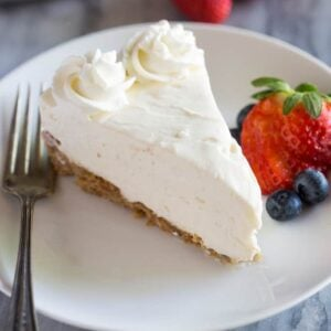 A slice of No-Bake Cheesecake on a white plate with a fork and berries on the side.