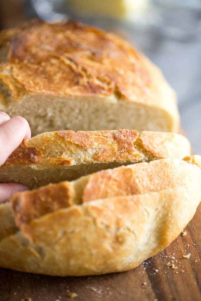 Close up photo of a loaf of no knead bread and a hand removing a slice.