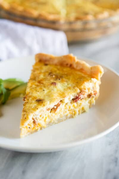 A slice of quiche lorraine on a white plate with sliced avocados on the side.