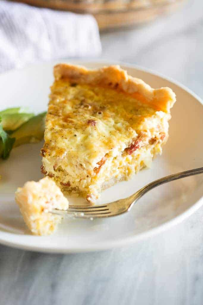 A slice of quiche lorraine with a fork removing a bite.