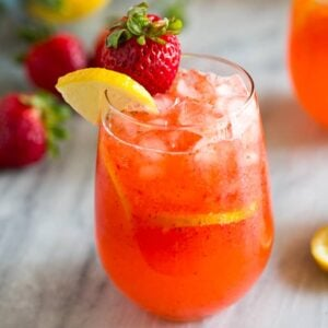 A glass of strawberry lemonade with a strawberry and lemon slice on the cup rim and strawberries and lemons in the background.