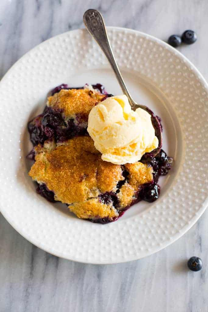 Overhead photo of a white bowl with blueberry cobbler with a scoop of vanilla ice cream on top