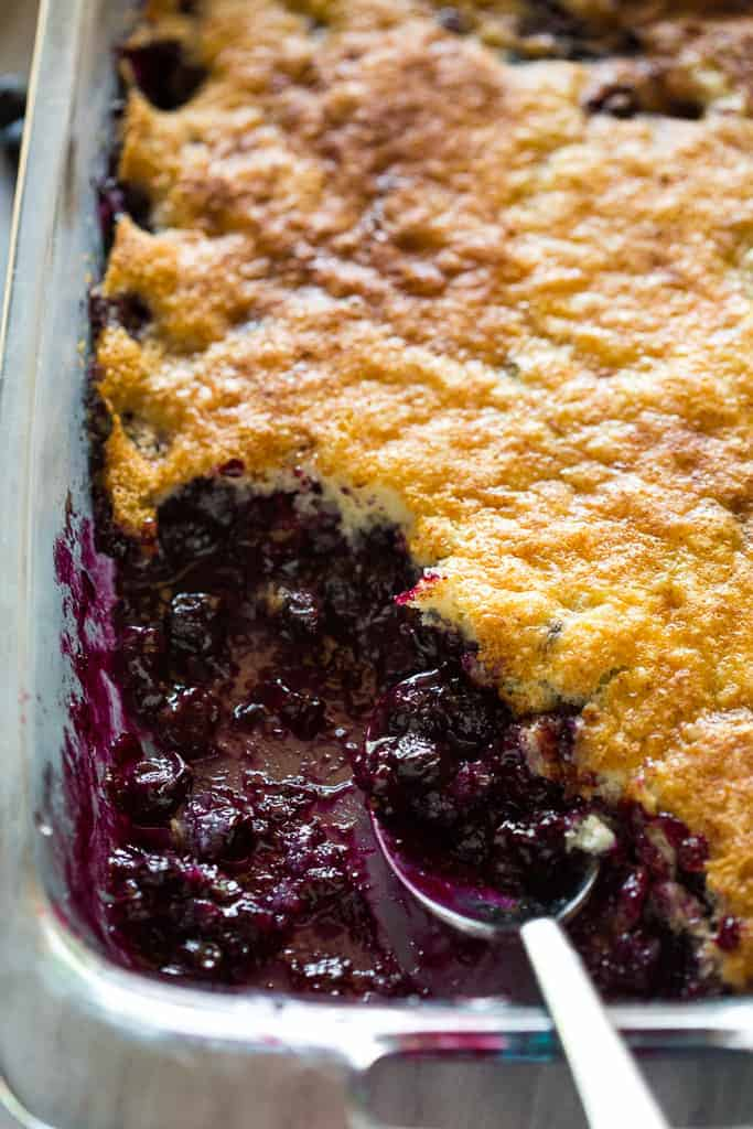A 9x13 inch pan of blueberry cobbler with a scoop removed.