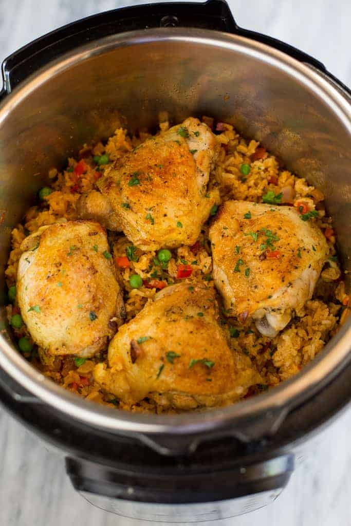 Close up photo of cooked chicken thighs on top of Spanish rice in an instant pot.