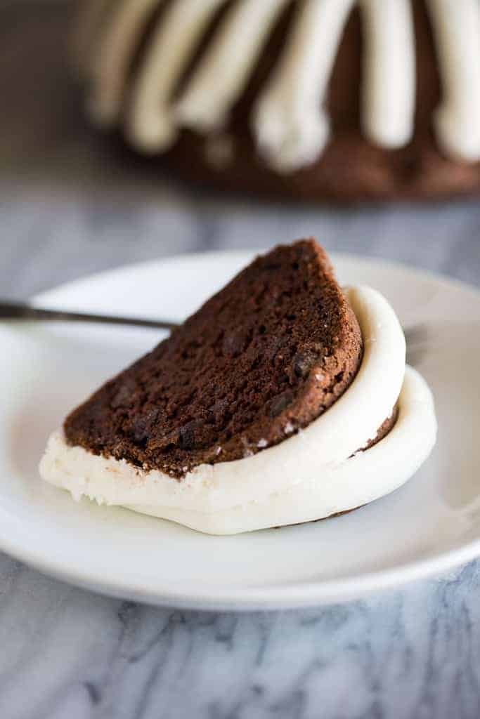 A slice of chocolate bundt cake frosted with cream cheese frosting, served on a white plate with a fork.