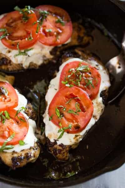 A cast iron skillet with chicken tenders layered with mozzarella, tomato and basil to make chicken caprese.