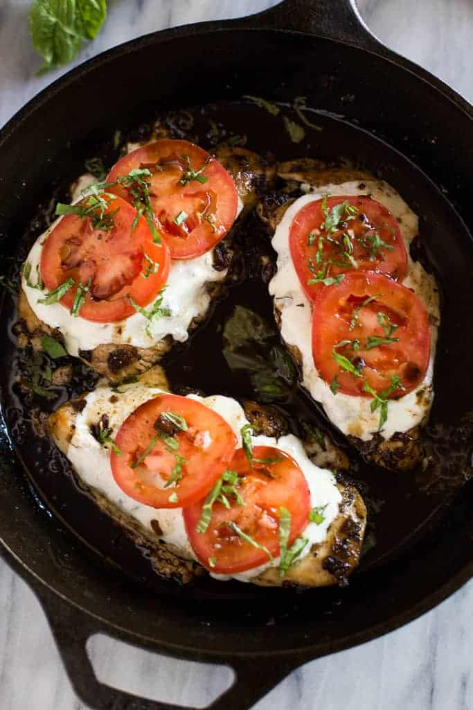 Overhead photo of baked chicken caprese in a cast iron skillet.