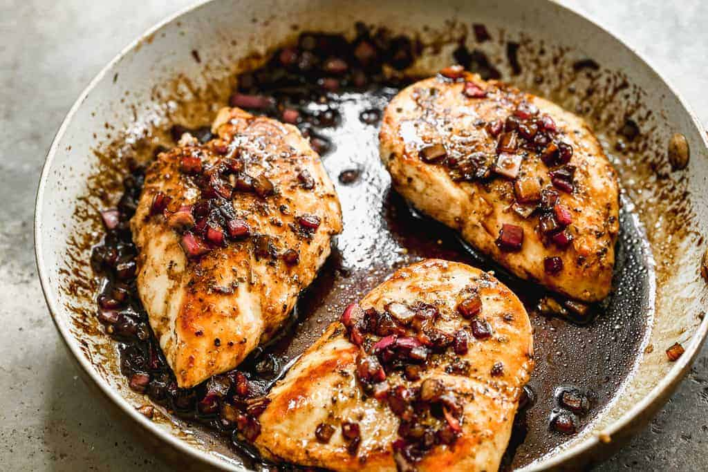 Chicken breasts in a skillet with balsamic reduction spooned on top.