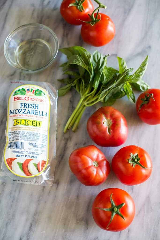 The ingredients for Caprese salad including fresh mozzarella, basil, tomatoes, and olive oil.