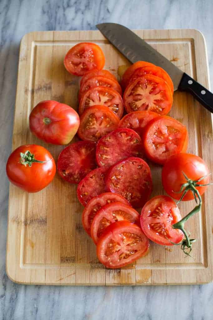 Slices of tomatoes on a cutting board.