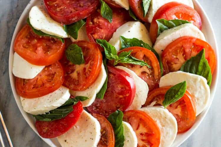 tomatoes, cucumbers, and mozzarella fanned out in a circle on a white plate.