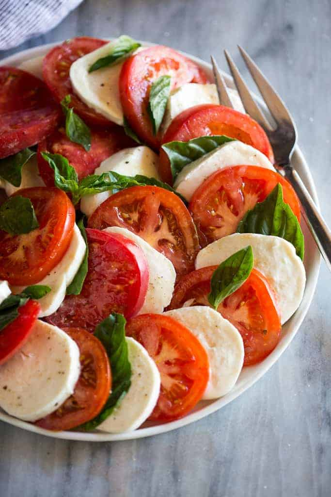 Caprese salad in a dish on a marble cutting board with a fork on the plate.