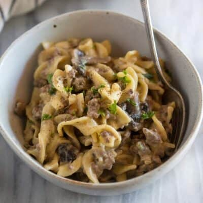 A bowl with hamburger stroganoff and a spoon.