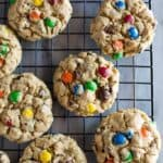 Monster cookies with m&m's on a wire cooling rack.