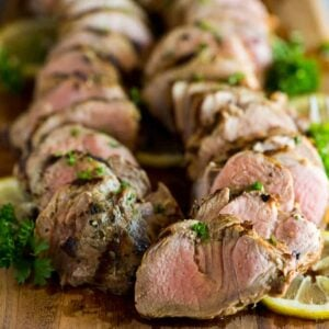 Sliced pork tenderloin on a cutting board, garnished with chopped parsley and lemon slices.