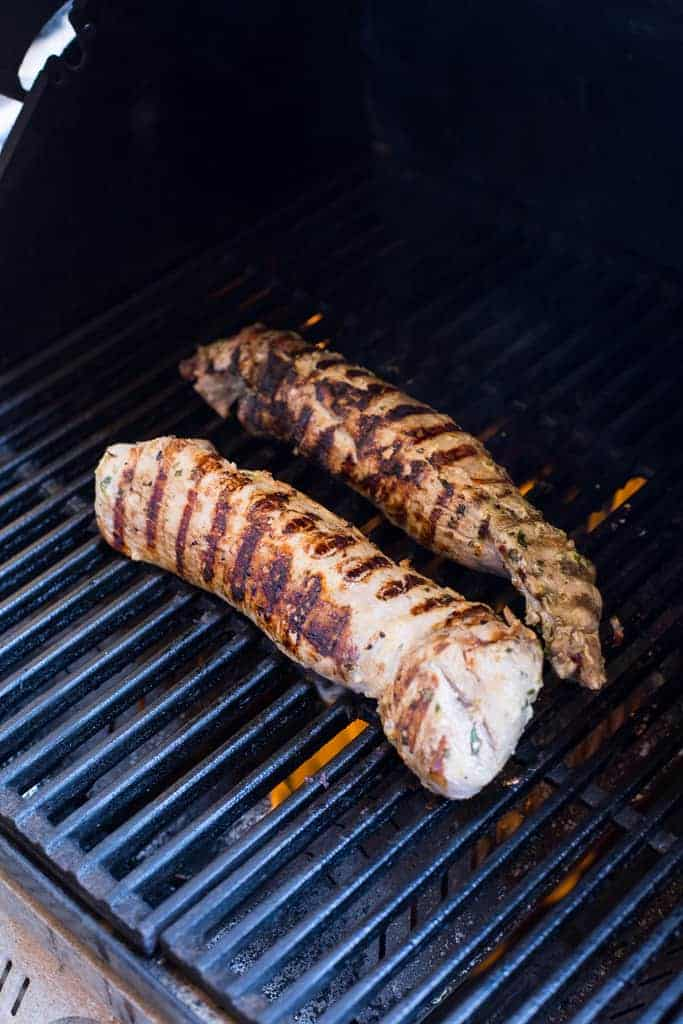 Two pork tenderloins being seared on a gas grill.