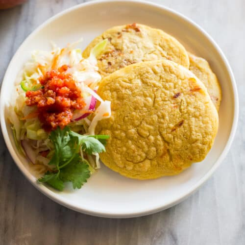 Three bean and cheese pupusas on a white plate with curtido cabbage relish and red salsa served on the side.