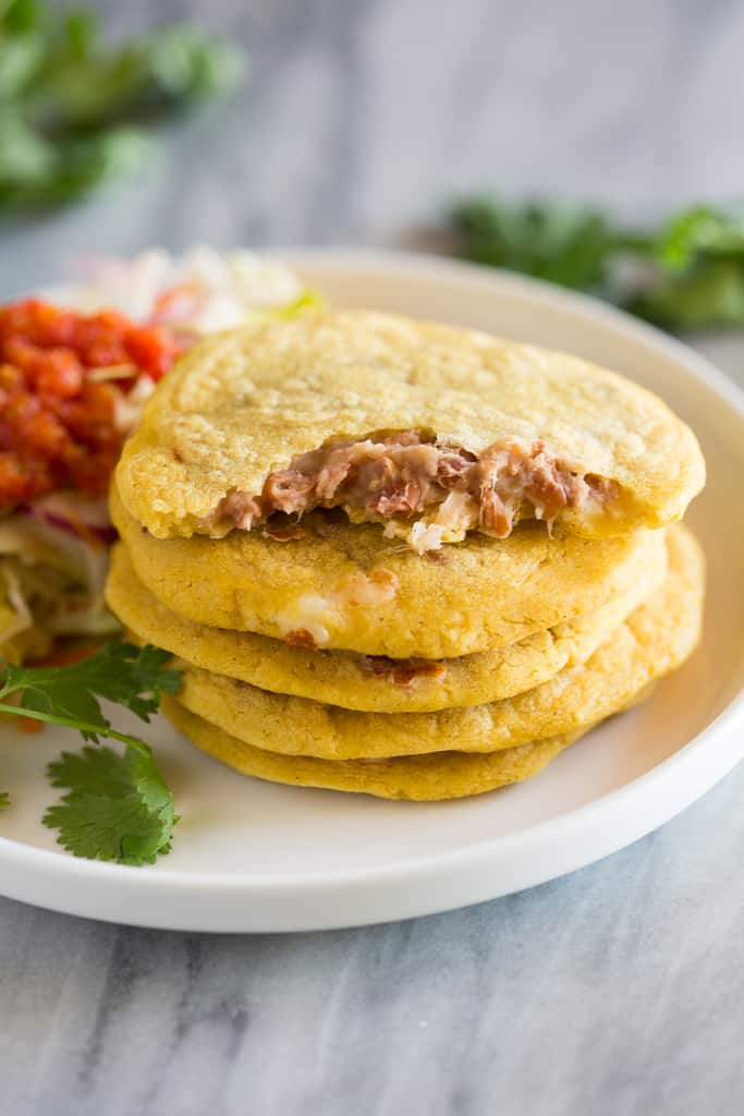 A stack of five pupusas with the top one half eaten and bean and cheese filling showing.