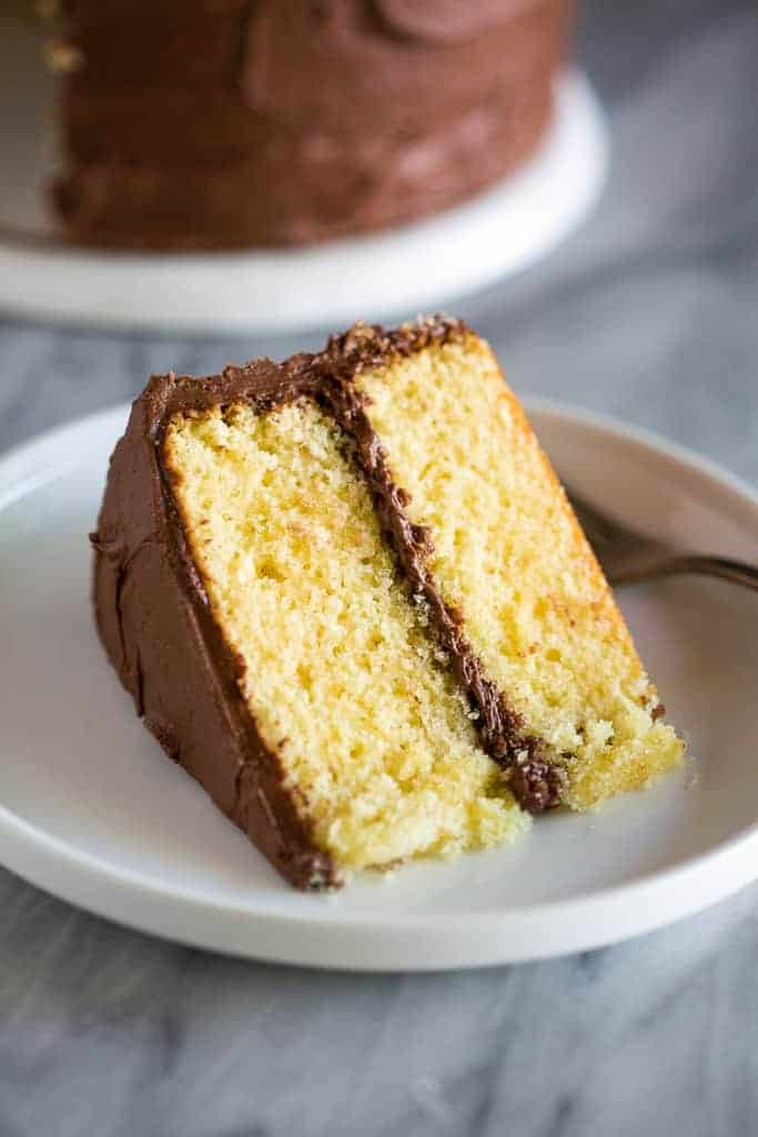 A slice of yellow cake with chocolate frosting served on a white plate.