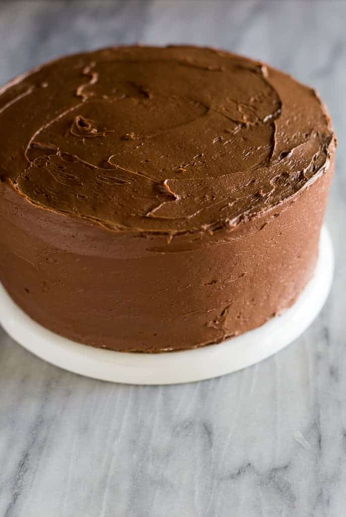 A two-layer cake with homemade chocolate frosting, served on a white plate.